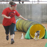 K9 Xpress member running as their dog comes out of a tunnel